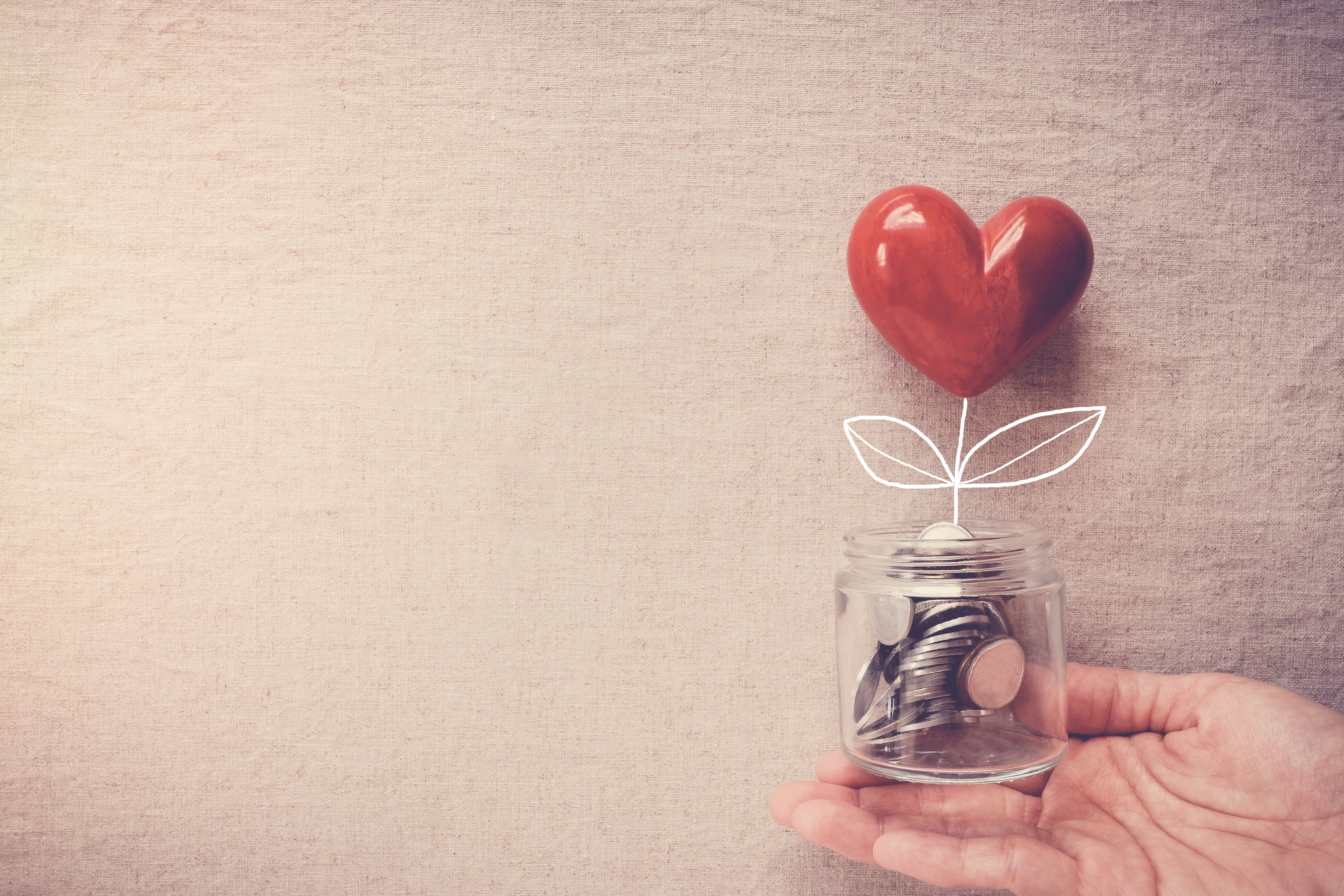 a hand holding a jar of money with a heart shape growing out of it
